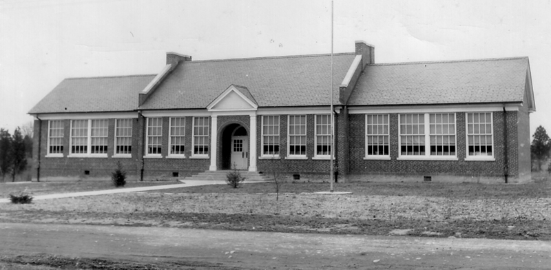 Black and white of Woodlawn Elementary School taken in 1958 for the Fairfax County School Board's fire insurance survey of school properties. The building looks much the same as it did in the 1940s. Trees have been planted on the grounds, but they are not large yet. The building has an arched entryway between two white columns. Large windows face the street which remains unpaved.