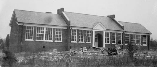 Black and white photograph of the new, brick Woodlawn Elementary School, circa 1941, during construction of two additional classrooms to the building. Construction debris is scattered about the school grounds.
