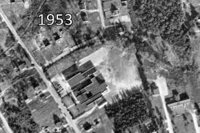 Black and white aerial photograph of Woodlawn Elementary School taken in 1953. Several additions have been constructed onto the rear of the original school building. The overall size of the building is less than half of what it present today.