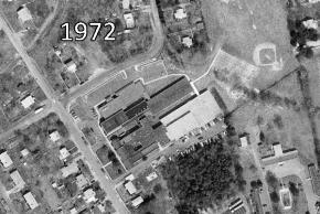 Black and white aerial photograph of Woodlawn Elementary School taken in 1972. Two large wings have been added to the rear of the building. Behind the school, a large area that was forested in the last picture has been cleared and turned into baseball playing fields.