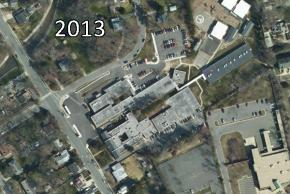 Color aerial photograph of Woodlawn Elementary School taken in 2013. A new parking lot section has been added. The building has been further enlarged by three large mobile classrooms and two more trailers.